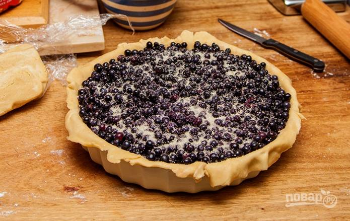 5. Тесто разделите на два части (отщипните еще кусочек, если хотите сделать украшения на пироге). Раскатайте тонко и выложите на дно жаропрочной формы. Сверху высыпьте ягоды, добавив по вкусу сахар при желании.