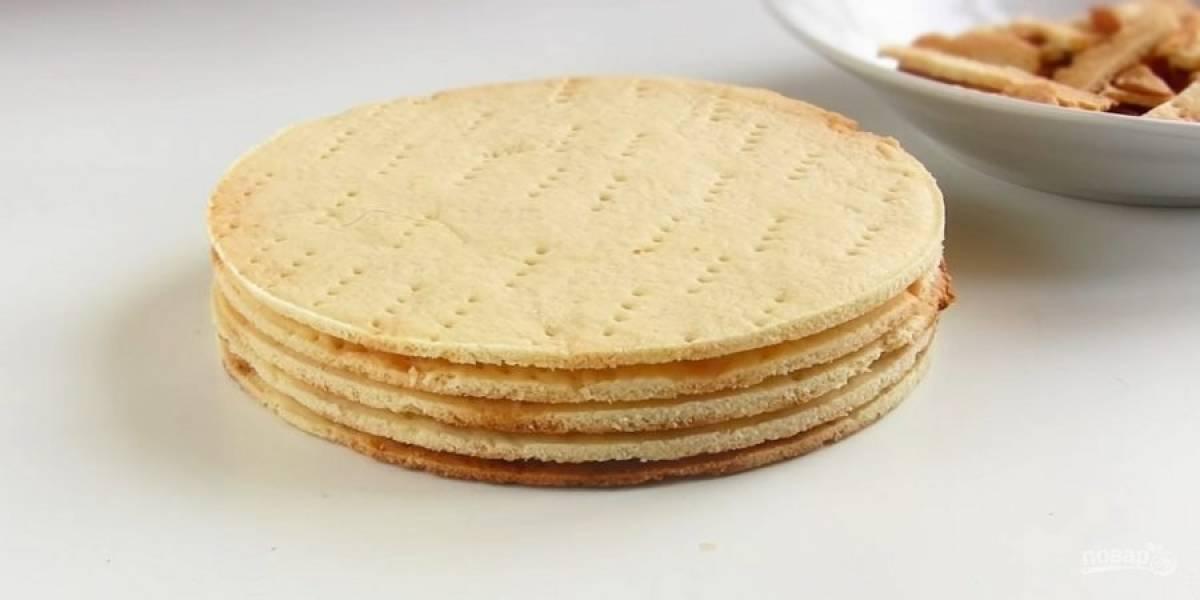 6. Наколите тесто вилкой и выпекайте в разогретой до 200 градусов духовке 6-8 минут. Горячие коржи обрежьте по размеру формы. Охлажденный крем взбейте миксером, обильно смажьте им остывшие коржи.