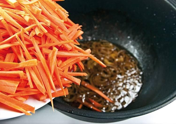 7. Вытаскиваем мясо и оставляем один жир в казане. Теперь шинкуем лук и жарим его, после чего шинкуем соломкой морковь и отправляем ее к луку.