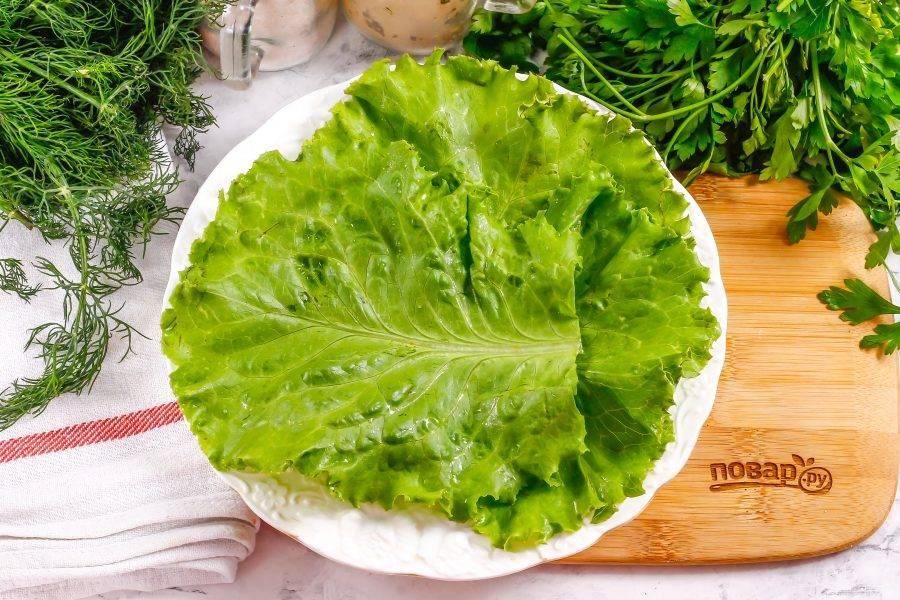 Промойте листья салата, стряхните лишнюю влагу и выложите их на тарелку.