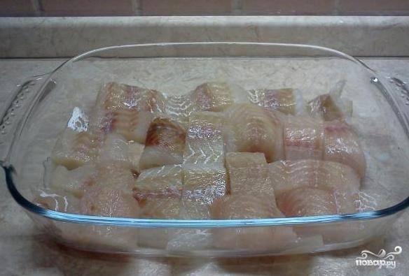 Размораживаем филе минтая, промываем, высушиваем, нарезаем на кусочки и выкладываем в форму для выпекания, посолив и поперчив по вкусу.