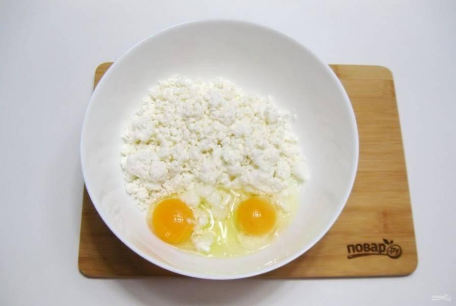 Разбейте в творог два яйца.
