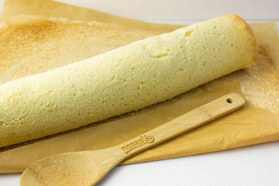 Переложите пергамент с бисквитом на рабочую поверхность. Аккуратно снимая бисквит с пергамента, сверните его в рулет. Это нужно делать сразу после выпекания, пока бисквит теплый и податливый. Оставьте рулет в таком виде остывать, а мы приступим к приготовлению крема.