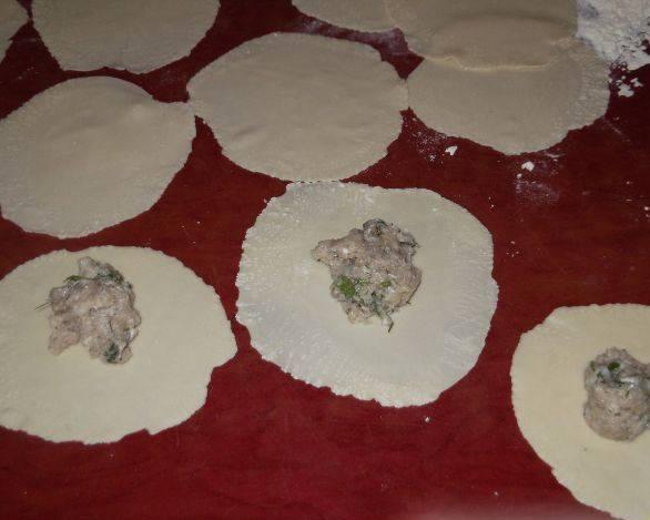 3. Теперь тесто достаем, раскатываем в лепешку, и при помощи тарелок или чашек вырезаем кружочки. По центру каждого - начинку. Защипываем края.