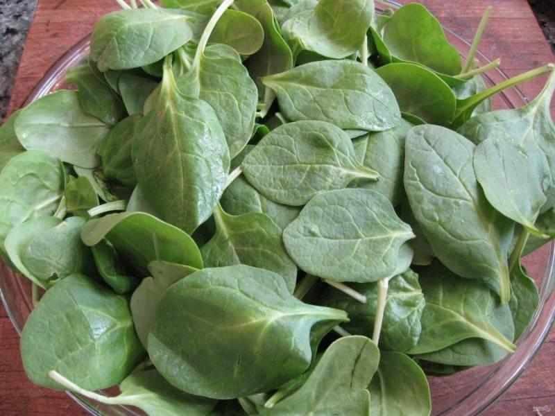 Листья шпината вымойте и обсушите. Когда они полностью высохли, выложите их в салатницу.