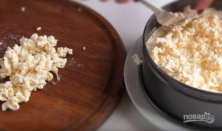 6. Плавленый сырок отправьте в морозилку на несколько минут, натрите на крупной терке и выложите четвертым слоем. Также смажьте майонезом. Отправьте салат на час в холодильник, чтобы он пропитался.