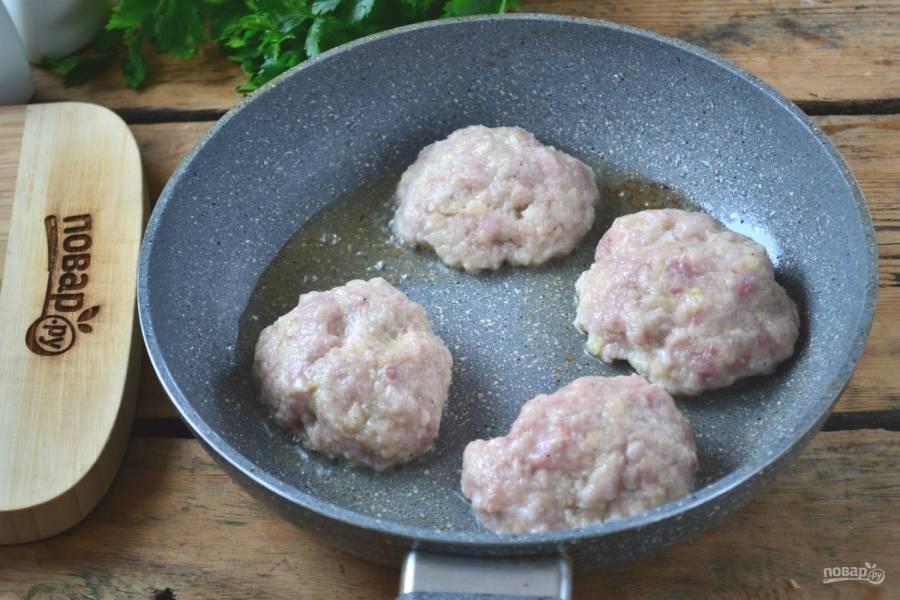 Руки смочите в воде. Сформируйте небольшие котлетки, которые затем выложите на сковороду. Жарьте под крышкой по 5-7 минут с каждой стороны (на медленном огне).