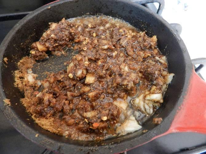 5. Чеснок очистить и мелко нарезать. На отдельной сковороде разогреть немного масла и отправить туда чеснок. Когда чеснок поджарится, добавить в сковороду специи, перемешать и отправить все содержимое в сотейник.