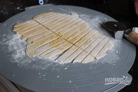 Раскатайте колобки на доске в пласт толщиной  0,5 см. Острым ножом разрежьте на полосочки.
