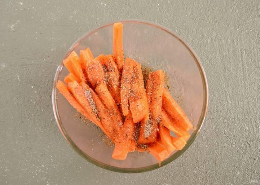 Посыпьте сверху специями и солью. Перемешайте так, чтобы полностью покрыть ими морковь.