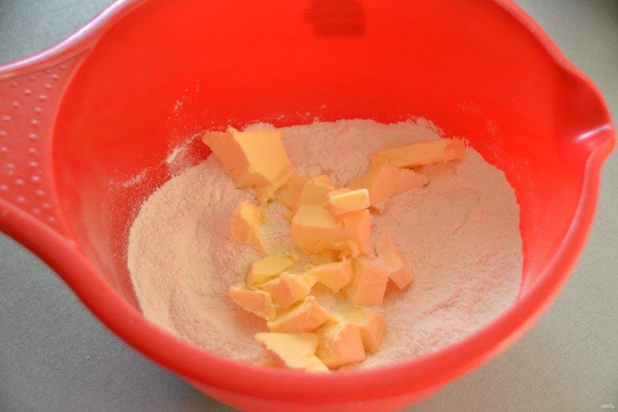 Добавьте к муке охлажденное сливочное масло, порезанное кубиком.