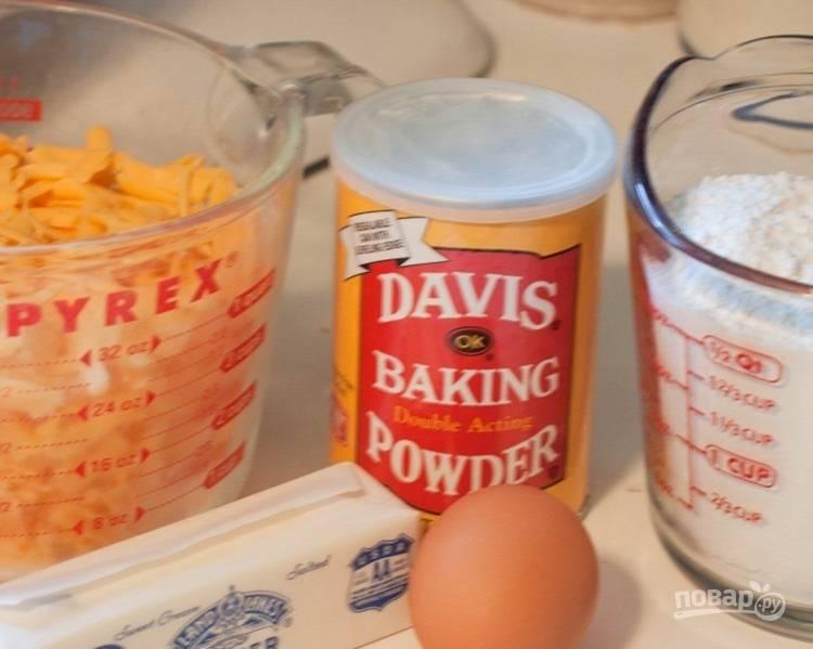 1.Смешайте муку с разрыхлителем и солью. В другой емкости смешайте сливочное масло комнатной температуры и тертый сыр. Соедините сухие ингредиенты с масляно-сырной смесью, добавьте по 1 ложке холодной воды и замесите тесто.