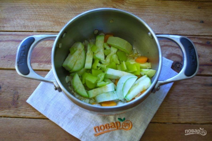 К обжаренному луку добавьте морковь, перец и кабачок. Обжарьте все вместе 5-7 минут на среднем огне.