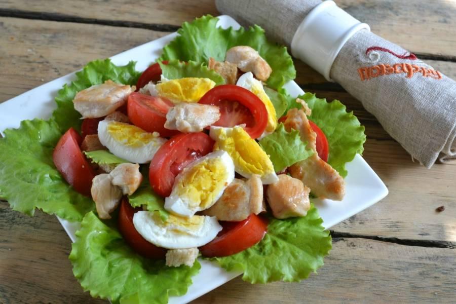 5.Соберите салат. На дно тарелки положите промытые листья салата, сверху положите помидоры, сухарики, порезанные дольками яйца и кусочки курицы.