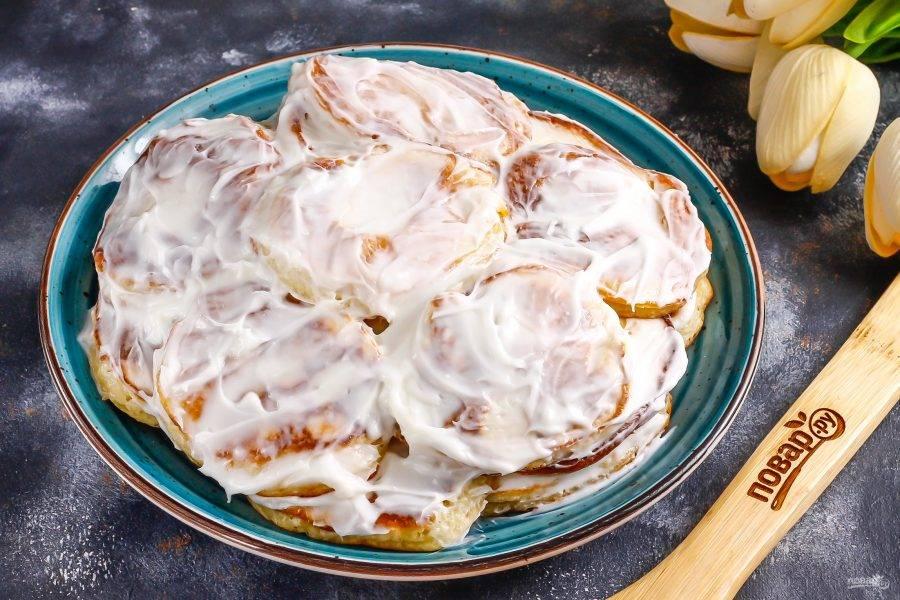 Обмажьте каждый оладушек сметанным кремом и выложите их на тарелку, сформировывая торт как можно круглее и ровнее. Отверстия между оладьями тоже промажьте кремом.
