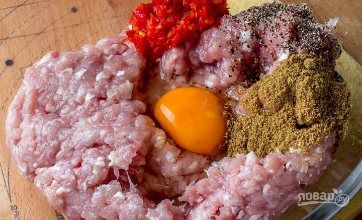4. В глубокой миске соедините фарш и лук, вбейте яйцо, добавьте специи по вкусу.