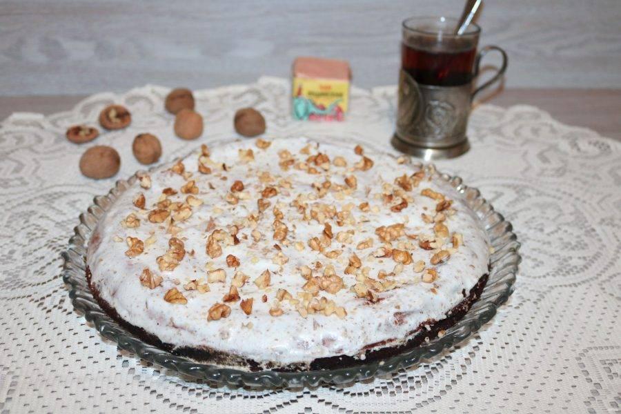 Соедините две половинки бисквита. Верх промажьте кремом, посыпьте оставшимися орехами.