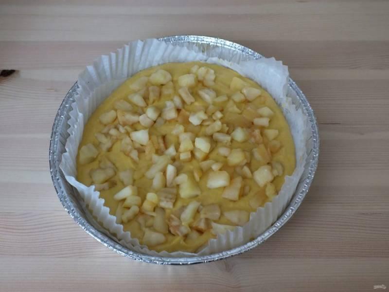Разогрейте духовку до 180 градусов. Возьмите форму диаметром 22 см. Выстелите пекарской бумагой. Выложите 1/2 теста. На него выложите обжаренные яблоки.