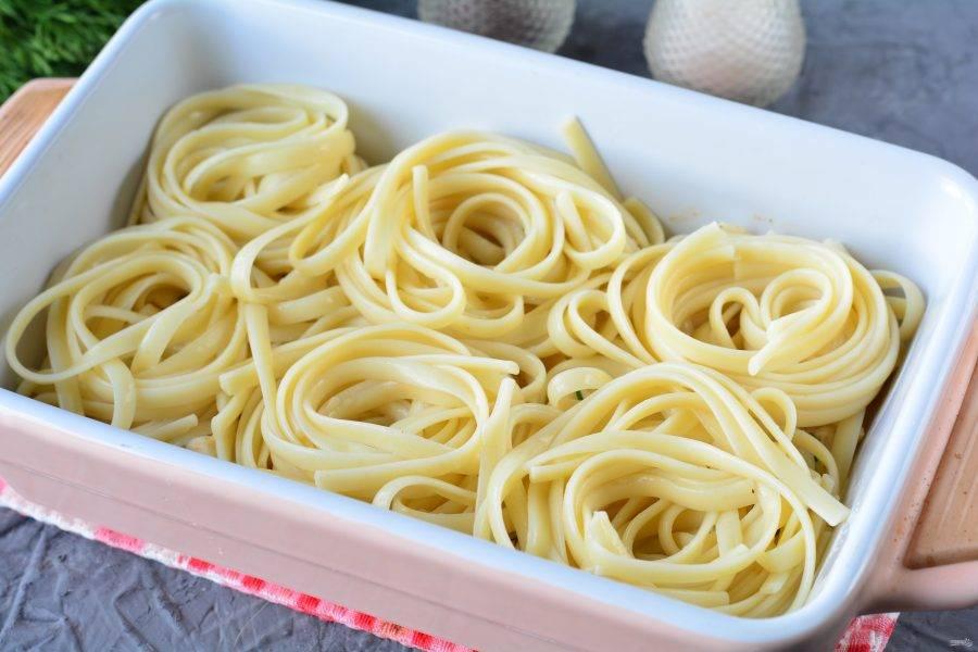 """При помощи ложки и вилки скрутите лапшу, чтобы получились """"гнезда"""", выложите в форму для запекания, смазанную маслом."""