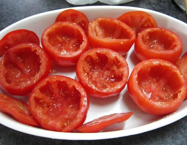 С помидоров срезаем верхушку, аккуратно выковыриваем из них мякоть. Посыпаем помидоры внутри солью, оставляем их на пару минут, это позволит вытянуть из помидоров лишнюю жидкость, ее потом нужно будет слить.