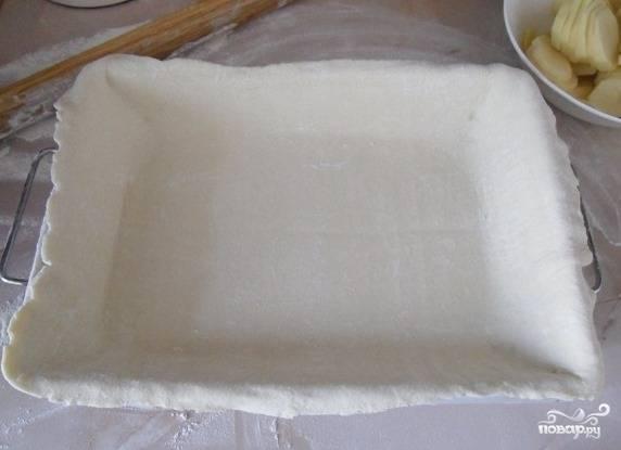 Разморозьте слоеное тесто. Сначала раскатайте один из двух пластов, а затем поместите его на противень. Тесто можно приготовить самостоятельно, но гораздо удобнее использовать уже готовое из магазина.