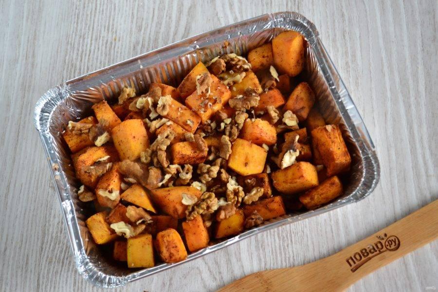 Запеките тыкву в духовке при температуре 190 градусов в течение примерно 20 минут. Затем извлеките форму из духовки, добавьте орехи. Их можно измельчить в крошку, а можно оставить достаточно крупными.