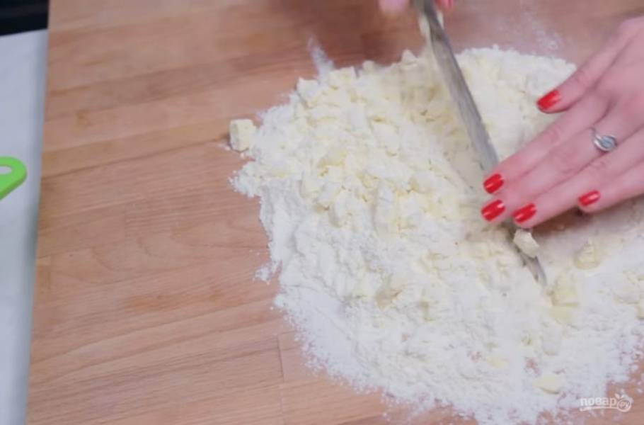 1. Сливочное масло нарежьте кубиками и уберите в морозильник на 15 минут. Затем с помощью ножа измельчите масло с мукой в мелкую крошку, не касаясь ее руками.
