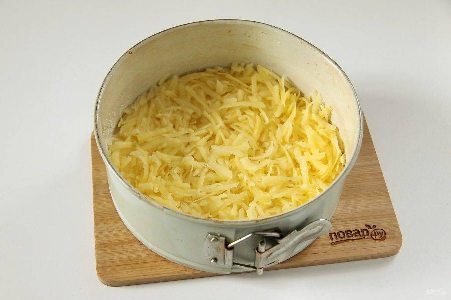 Картофель натрите на крупной терке, отожмите и распределите сверху.