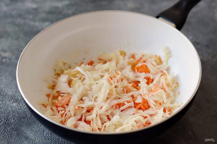 Добавьте квашеную капусту. Если она длинная, можно предварительно ее нарезать. Тушите все вместе минут 5.