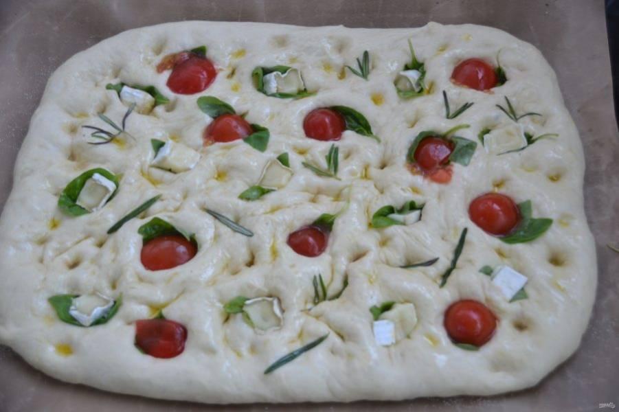 Выложите на противень тесто, предварительно раскатанное в пласт. Пальцами сделайте ямки,  сбрызните оливковым маслом, выложите листочки базилика, прямо в них вдавите половинки помидорок черри или кусочки сыра, выложите листочки розмарина.