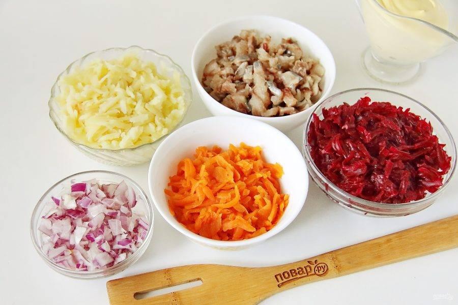 Все овощи очистите и натрите на крупной терке. Лук нарежьте кубиками, если используете обычный лук, то ошпарьте его кипятком. Сельдь разделайте на филе и нарежьте небольшими кубиками.