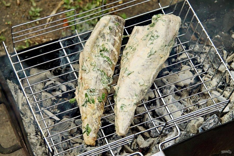 Замаринованную рыбу выложите на решетку гриль, которую предварительно необходимо смазать маслом.
