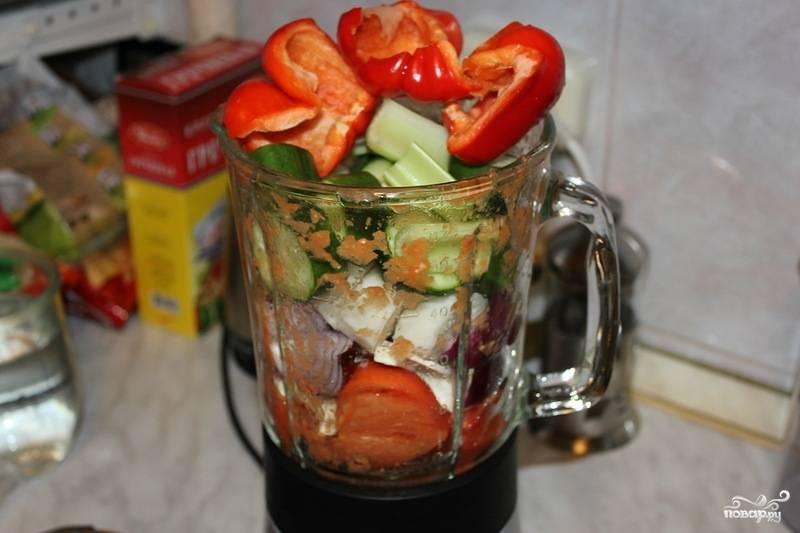 Теперь пришло время превратить остальные овощи в пюреобразную массу. Очистите и нарежьте красный лук, болгарский перец и огурцы. С огурцов можно не снимать кожицу. Сложите всё в блендер и превратите в пюре.