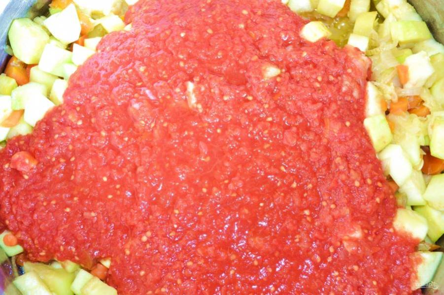 Влейте томат, перемешайте и оставьте тушиться на медленном огне часа на 4. Помешивайте периодически, чтобы овощи не пригорели.