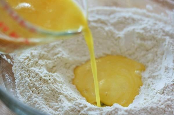 1. Дрожжи залить теплой водой и всыпать щепотку сахара. Оставить на 10 минут, чтобы они начали работать. Тем временем можно просеять в глубокую мисочку муку со щепоткой соли и сахар. Растопить сливочное масло с молокой (не доводя до кипения), немного остудить и вбить яйцо. Тщательно взбить массу и влить в мисочку с мукой, предварительно сделав там углубление.