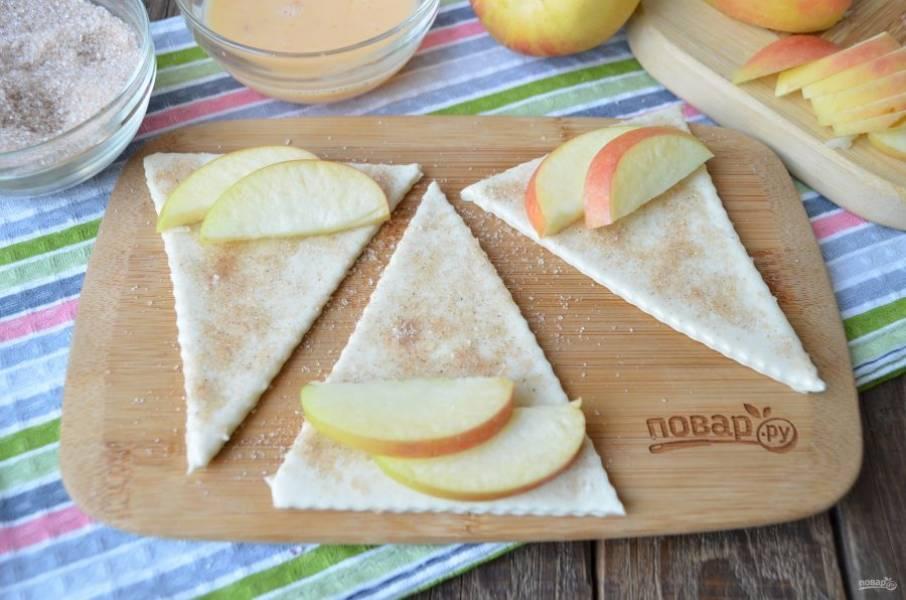 Яблочко порежьте так, чтобы каждую половинку можно было порезать на тонкие дольки, но не менее 5 мм. Положите по 2-4 дольки на каждый треугольник (в зависимости от размера теста).