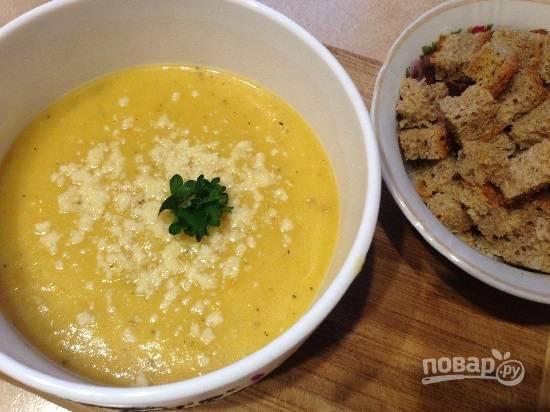 И можно приступать к трапезе. Я посыпаю суп мелко натертым твердым сыром и подаю его к столу с сухариками и зеленью.