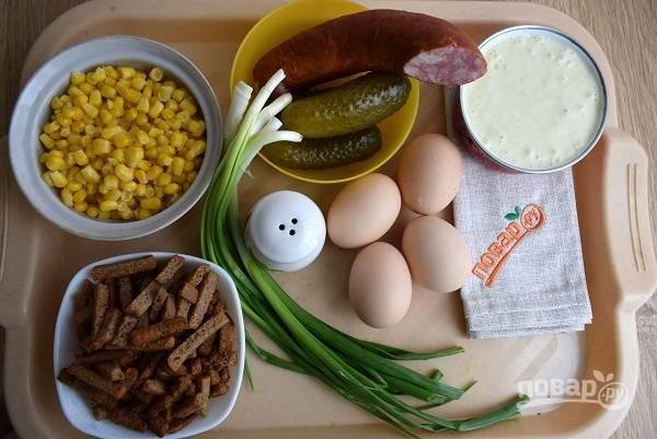 Подготовьте необходимые ингредиенты. Отварите яйца, сухарики высыпьте из пакета. Отложите несколько для украшения. Кукурузу слейте и откиньте на сито. Лук промойте.