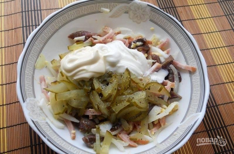 В салат добавьте нарезанный огурец, соль, перец, сметану и майонез.