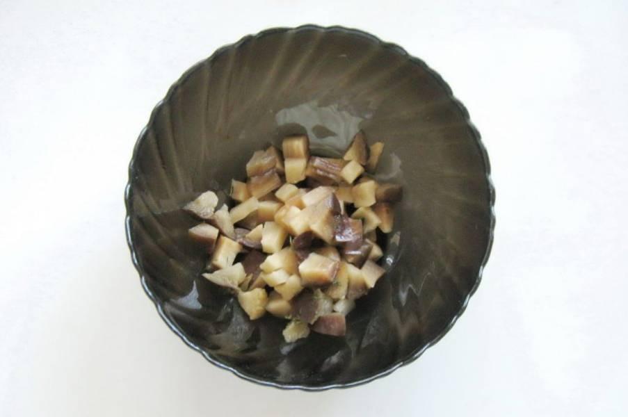 Соленые баклажаны нарежьте мелкими кубиками и выложите в салатник.