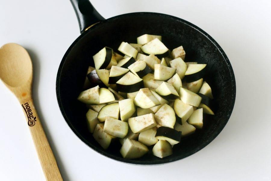 Баклажаны разрежьте вдоль пополам, затем еще раз разрежьте на две половинки и нарежьте четвертинками. Выложите на разогретую сковороду с маслом.