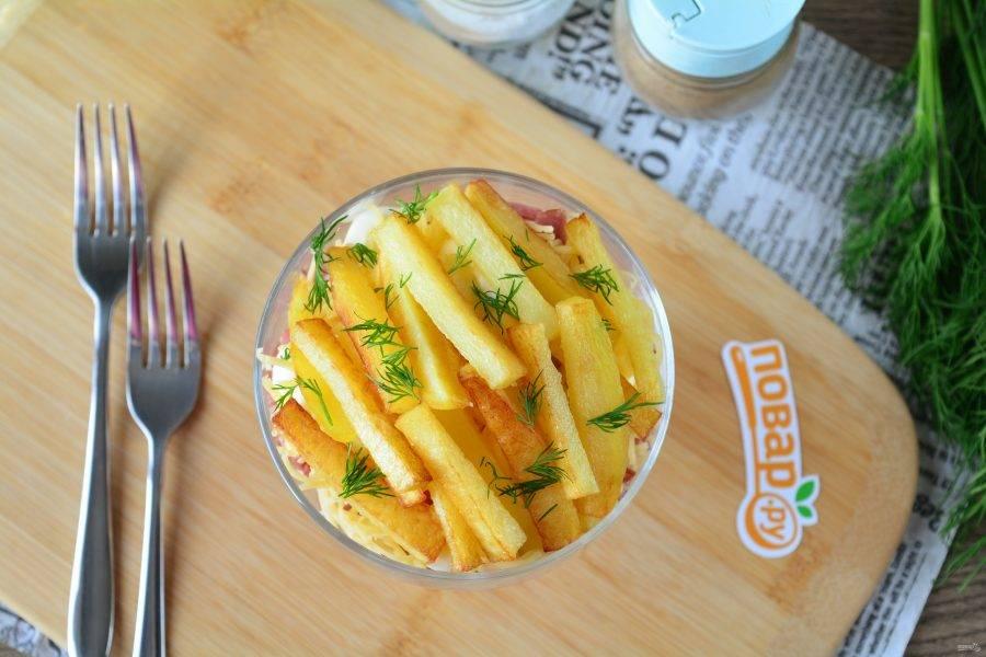 Завершите собирать салат слоем картошки фри. Готово. Подавайте к столу. Приятного аппетита!