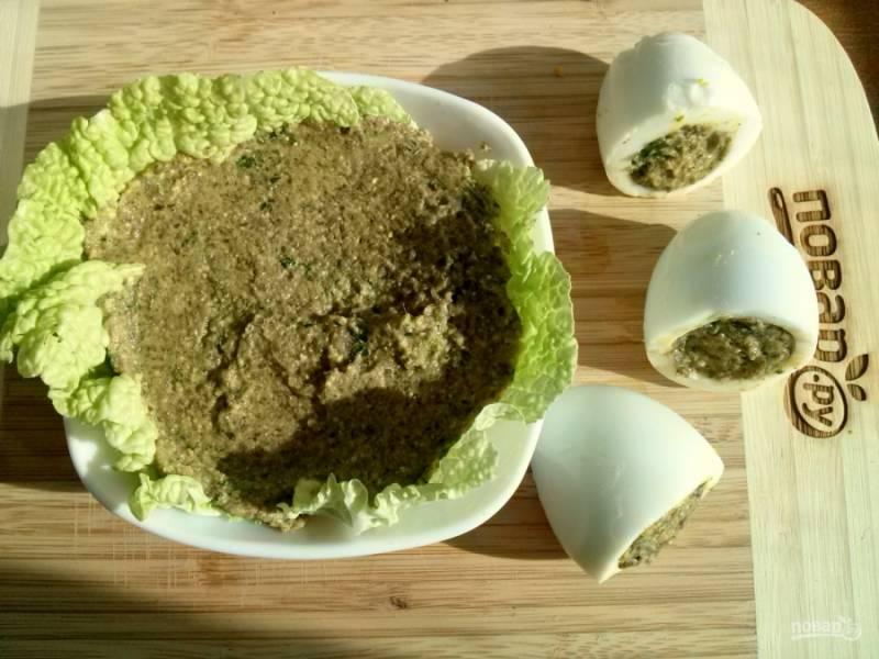 Выложите в салатницы по 1-2 листа пекинской капусты. Пустые белки нафаршируйте грибным паштетом, оставшийся паштет выложите поверх капустных листьев.