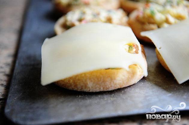 5. Поставить противень в духовку на 5 минут, затем вынуть противень и положить кусочек сыра на каждую булочку. Вернуть противень в духовку и запекать булочки до готовности, пока сыр не расплавится и не начнет бурлить. Убрать булочки из духовки, дать немного остыть и сразу же подавать.
