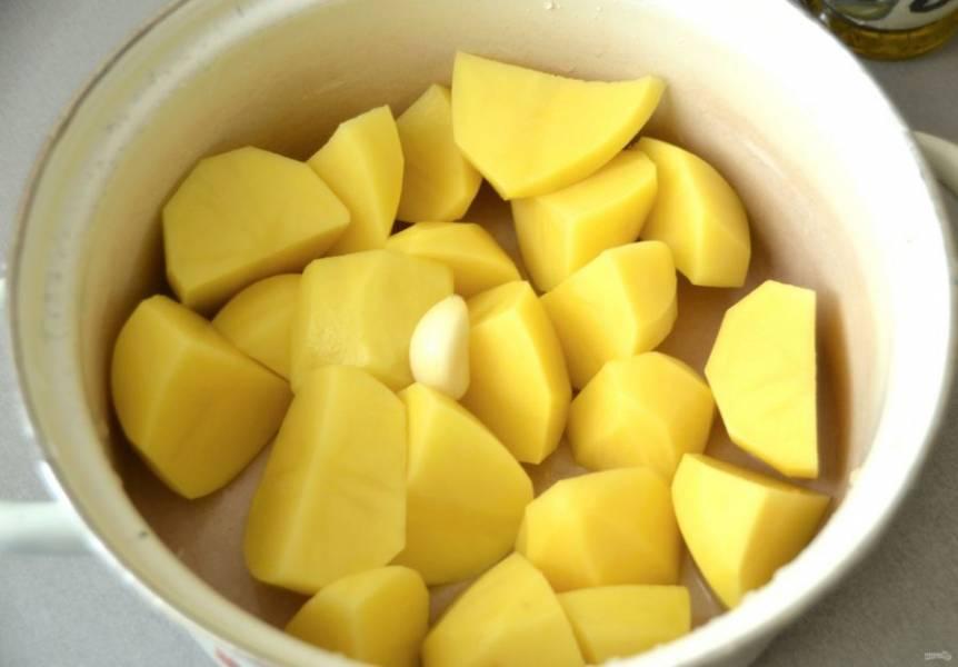 Очистите картофель, порежьте на крупные дольки и отварите до готовности с зубчиком чеснока, посолите.