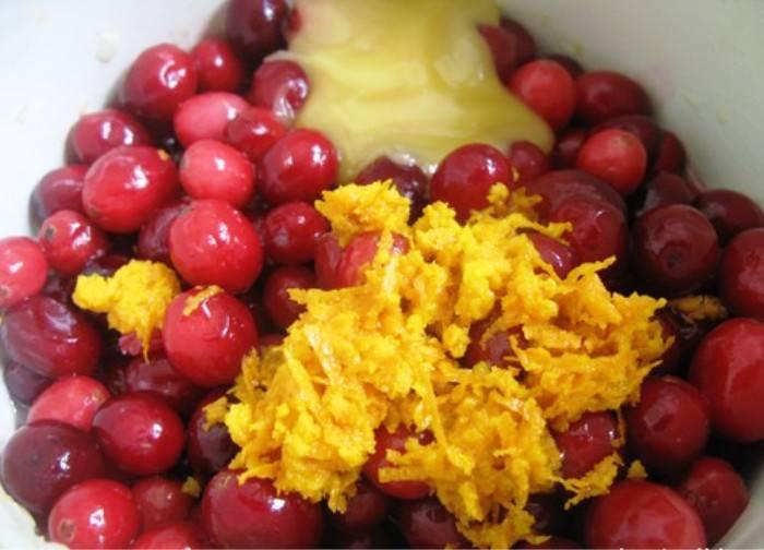 Добавьте к луку клюкву, мед, цедру и сок апельсина. Закройте крышкой и варите 15 минут. Затем еще 5 минут при открытой крышке и непрерывном помешивании.