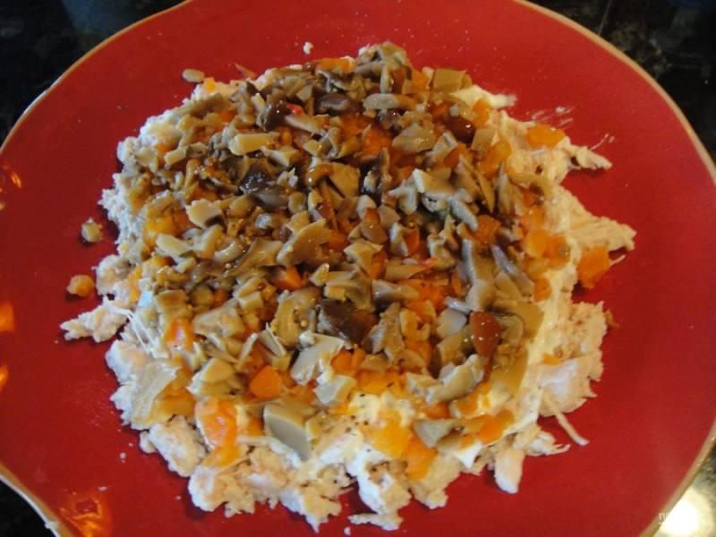 2.Отварите морковь и яйца, затем остудите и очистите, нарежьте небольшими кубиками только морковь. Уложите поверх курицы морковь, посолите, затем смажьте тонким слоем майонеза. Нарежьте кусочками маринованные грибы и выложите их поверх майонеза.