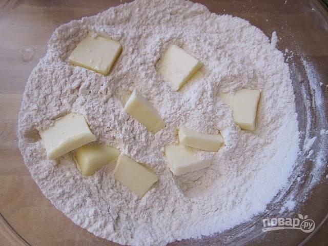 3.Нарежьте сливочное масло кусочками и выложите в мучную смесь.