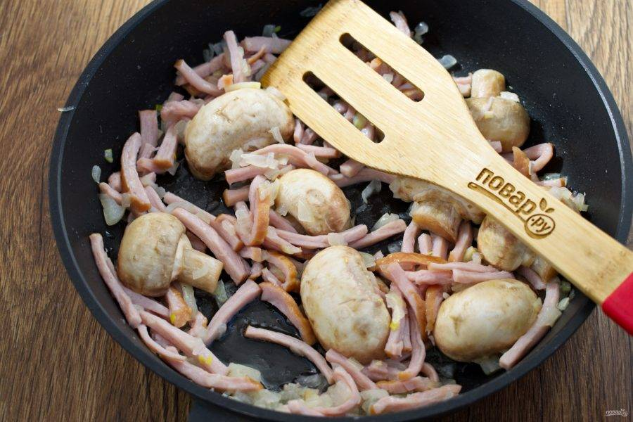 На сковороде разогрейте растительное масло, пассеруйте лук до прозрачности. Копченную ветчину (мясо или бекон) нарежьте тонкой соломкой, грибы разрежьте пополам. Добавьте ветчину и грибы к луку, обжаривайте 2 минуты.