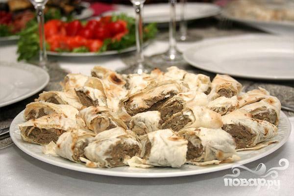 6.Армянский лаваш намазываем получившимся паштетом, от одного края приблизительно пятнадцать сантиметров. Заворачиваем, а лишний край отрезаем. Перед самой подачей колбаску нарезаем кусочками по два – два с половиной сантиметра.